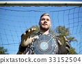 goalkeeper or soccer player at football goal 33152504