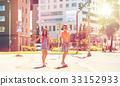 teenage couple riding skateboards on city street 33152933