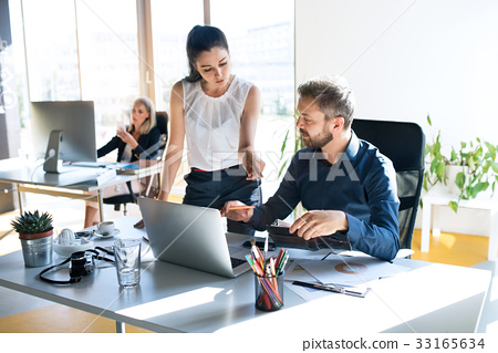 Three business people in the office working 33165634