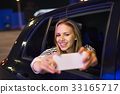 Woman with smartphone in her car at night. 33165717