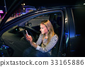Woman with smartphone in her car at night. 33165886
