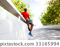 Afro-american runner in the city sitting on 33165994