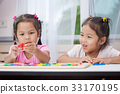 Two asian girls play and learn magnetic alphabets 33170195