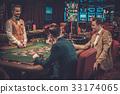 Upper class friends gambling in a casino. 33174065