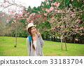 happy woman standing in front of cherry tree 33183704