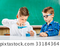 Two pupils pouring liquid in glass in school 33184364