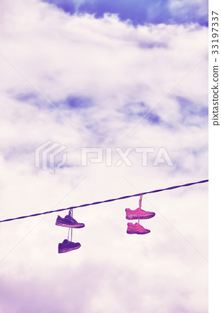 Old shoes hang on wire. 33197337