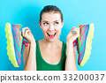 Happy young woman holding shoes  33200037