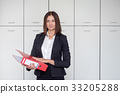 Young happy businesswoman holding red folder and 33205288