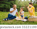 Happy lovely family eating sandwiches on picnic 33221100