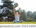 Upbeat girl throwing a ball in the air 33221404