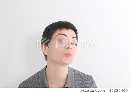 Cute charming short hair woman blowing air kiss at 33223490