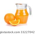 Orange juice in pitcher and oranges. 33227042