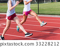 Two high school girls do running drills on a track 33228212