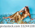 Young woman posing in golden dress with crown 33244108