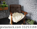 An old leather armchair with a rug and baskets 33253168