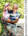 Grandpa laughing on bicycle with granddaughter 33254198
