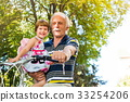 Grandpa riding bicycle with granddaughter in hands 33254206