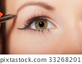 Girl tweezing eyebrows closeup 33268201