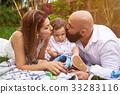 Parents kissing his son 33283116
