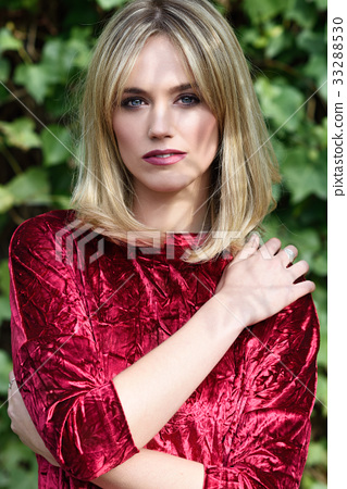 Beautiful young blonde woman in green leaves background 33288530