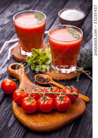 Glass of fresh tomato juice and tomatoes on a 33295437