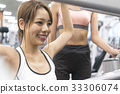 Young woman receiving weight training instructions at the gym 33306074