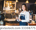 Asian female barista wear jean apron hold tablet 33308775