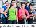 Group of women and men in gym posing at fitness 33320107