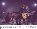 Musician duo band singing a song and playing music instrument with Fellow band musicians on black background with spot light and lens flare, musical concept 33323549