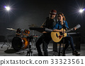 Musician duo band singing a song and playing music instrument with Fellow band musicians on black background with spot light and lens flare, musical concept 33323561