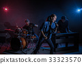 Musician band hand holding the microphone and singing a song and playing music instrument with Fellow band musicians on black background with spot light and lens flare, musical concept 33323570
