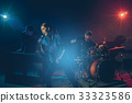 Musician band hand holding the microphone and singing a song and playing music instrument with Fellow band musicians on black background with spot light and lens flare, musical concept 33323586