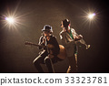 Musician Duo band playing a Trumpet and singing a song and playing the guitar on black background with spot light and lens flare, musical concept 33323781