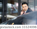 a businessman is getting off car and smiling 33324096