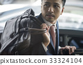 a businessman is holding bag and getting off car 33324104