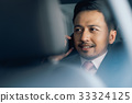 an elegant man is calling and smiling in car 33324125