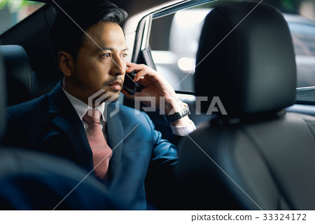 The portrait of man sitting in the car and talking on phone 33324172