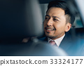 The portrait of a businessman sitting and smiling in the car 33324177