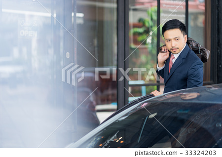 The picture of a businessman holding a bag and standing near the car 33324203