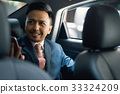 The portrait of man smiling and talking to someone on a car 33324209