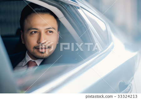 The portrait of a businessman looking out from the car 33324213