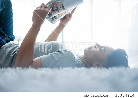 The picture of man lying on the floor and reading magazine 33324214