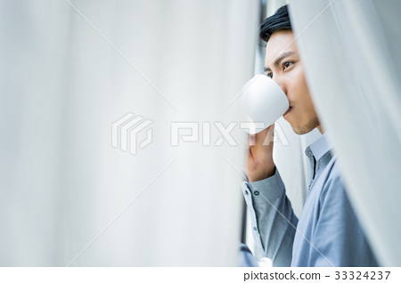 A portrait of a young man drinking coffee behind the curtain. 33324237
