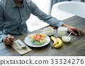 a photo of a man sitting at the table and eating breakfast 33324276