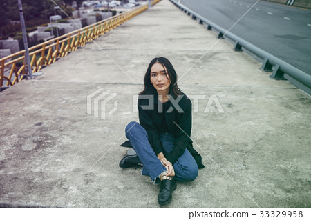 Asian ethnicity girl is on a bridge shoot. 33329958