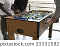 Group of guys playing foosball 33331592