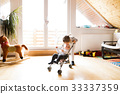 Little girl at home with baby brother in toy 33337359