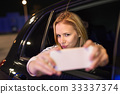 Woman with smartphone in her car at night. 33337374