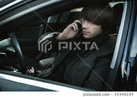 Handsome man using a smartphone in a car 33349193